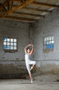 Beautiful ballerina in white dancing in abandoned building Royalty Free Stock Photo