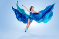 Beautiful ballet dancer flowing blue fabric dancing grace studio Stock Images