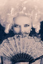 Beautiful baroque woman monochrome portrait with wig and fan style of a young behind a hand Royalty Free Stock Image
