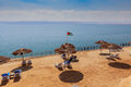 Beautiful beach with clean yellow sand and beach umbrellas on the Dead Sea shore. Royalty Free Stock Photo