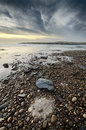 Beautiful beach scene full of pebbles in the coastline, natural circle formation in the sand Royalty Free Stock Photo