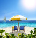 Beautiful beach with white sand two chairs umbrella and a sail yellow sailing boat in the sea Royalty Free Stock Photos