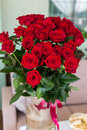 Beautiful big bouquet of roses in a vase standing on the table Royalty Free Stock Photo