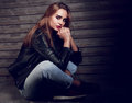 Beautiful biker woman thinking in black fashion jacket and jeans Royalty Free Stock Photo