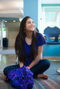 Beautiful biracial teen girl sitting crossed legged on floor smi Royalty Free Stock Photo