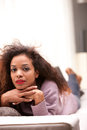 Beautiful black woman staring at camera afro american lying on a sofa Royalty Free Stock Image