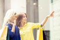 Beautiful blond and brunette shopaholic women pointing at showca Royalty Free Stock Photo