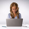 Beautiful blond business woman sitting behind her desk typing on her laptop computer Royalty Free Stock Photography
