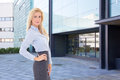 Beautiful blond business woman standing on street against office young building Stock Image