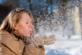 Beautiful blond young woman blowing Snow outdoors Royalty Free Stock Photo