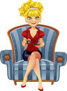 Beautiful blond girl in blue armchair with cup Royalty Free Stock Photo