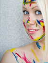 Beautiful blond girl with body art blue eyes and paints on her face Royalty Free Stock Image