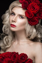 Beautiful blond girl in dress and hat with roses, classic makeup, curls, red lips. Beauty face. Royalty Free Stock Photo