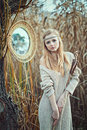 Beautiful blond girl with a mirror in the reeds Stock Photo