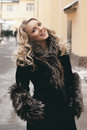 Beautiful blond girl portrait street in fur coat Stock Photo