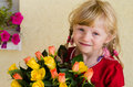 Beautiful blond girl with roses bunch of yellow and orange Royalty Free Stock Image