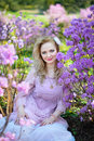 Beautiful blond girl among the spring flowering branches Royalty Free Stock Photo