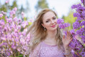 Beautiful blond girl among the spring flowering branches Stock Image