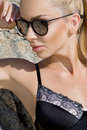 Beautiful blond hair sexy woman young girl model in sunglasses and elegant black swimsuit with crystals Royalty Free Stock Photo