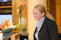 Beautiful blond hotel receptionist stylish standing behind the service desk in a lobby looking at the camera with a friendly Stock Photo