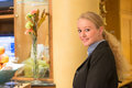 Beautiful blond hotel receptionist stylish standing behind the service desk in a lobby looking at the camera with a friendly Royalty Free Stock Photo
