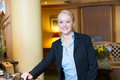 Beautiful blond hotel receptionist stylish standing behind the service desk in a lobby looking at the camera with a friendly Stock Photography