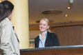 Beautiful blond hotel receptionist stylish standing behind the service desk in a lobby looking at a guest with a Royalty Free Stock Image