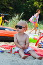 Beautiful blond little boy on the beach with sunglasses Royalty Free Stock Photography