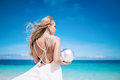 Beautiful blond long hair fiancee in a long white wedding dress stand on the white sand beach with a pearl. Looking to the sea. Bl Royalty Free Stock Photo
