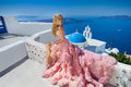 Beautiful blond runaway bride in white wedding dress fabulous with a very long train of crystals in the street on Santorini