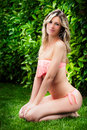 Beautiful blond slim girl in bikini on a lawn. Green park. Royalty Free Stock Photo