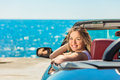 Beautiful blond smiling young woman in convertible top automobile looking sideways while parked near ocean waterfront Royalty Free Stock Photo