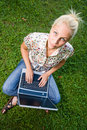 Beautiful blond using laptop outdoors in nature. Royalty Free Stock Image