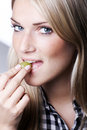 Beautiful blond woman biting a grape sensual cropped head portrait of she is holding between her teeth as she looks sideways at Stock Images