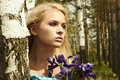 Beautiful blond woman with blue flowers in a forest portrait of Stock Images