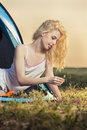 Beautiful blond woman camping dressed in night wear enjoying the early morning while playing with wheat in the entrance of a tent Royalty Free Stock Photos