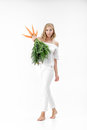 Beautiful blond woman  holding fresh carrot with green leaves on white background. Health and Diet Royalty Free Stock Photo