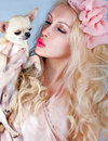 Beautiful blond woman kissing tiny chihuahua in hands Royalty Free Stock Image