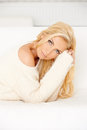 Beautiful blond woman lying on sofa she wearing warm cozy sweater Royalty Free Stock Image