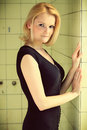 Beautiful blond woman in a old building dress posing shower stall cross processing fashion photography Royalty Free Stock Image