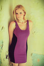 Beautiful blond woman in a old building purple dress posing cross processing fashion photography Royalty Free Stock Photography