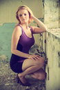 Beautiful blond woman in a old building purple dress posing she kneels at the window cross processing fashion photography Stock Photography