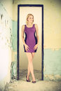 Beautiful blond woman in a old building purple dress posing she stands between the doorjamb cross processing fashion Royalty Free Stock Image