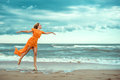 Beautiful blond woman in orange mini dress with flying train dancing barefoot on the wet sand at the storming sea Royalty Free Stock Photo