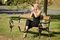 Beautiful blond woman painting her lips in the park Royalty Free Stock Photo