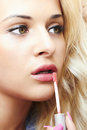 Beautiful blond woman paints lips with lipstick lip gloss portrait of Royalty Free Stock Photos