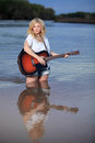 Beautiful blond woman playing acoustic guitar in water pretty caucasian a standing a river Stock Photos