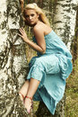 Beautiful blond woman sits on a tree in a forest blue dress Royalty Free Stock Images