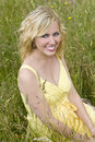 Beautiful Blond Woman Sitting In Tall Grass Stock Images