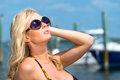 Beautiful blond woman in sunglasses and bikini relaxing and enjoying the summer sun at a tropical vacation with boats and marina Royalty Free Stock Image